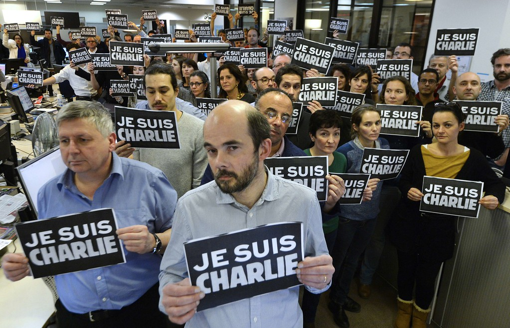 ". Journalists hold placard reading ""I am Charlie\"" as they hold a minute of silence, on January 7, 2015 at the redaction of French news agency Agence France Presse, following the attack by gunmen in the offices of the French satirical weekly Charlie Hebdo. Heavily armed gunmen massacred 12 people on Wednesday after bursting into the Paris offices of a satirical weekly that had long outraged Muslims with controversial cartoons of the prophet Mohammed. AFP PHOTO/BERTRAND GUAY/AFP/Getty Images"