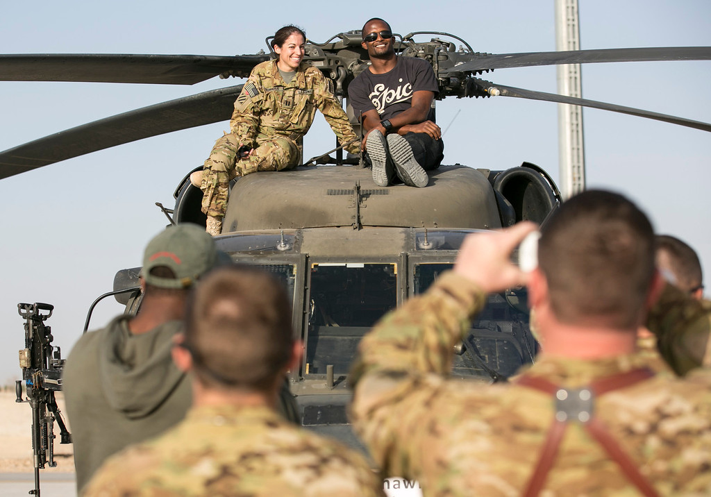 . Denver Broncos cornerback Champ Bailey poses for a photo sitting on top of a Blackhawk helicopter next to a service member stationed in the Middle East during a stop on his week-long USO/NFL tour March 17, 2013.  This is Bailey\'s first USO tour.  USO Photo by Fred Greaves