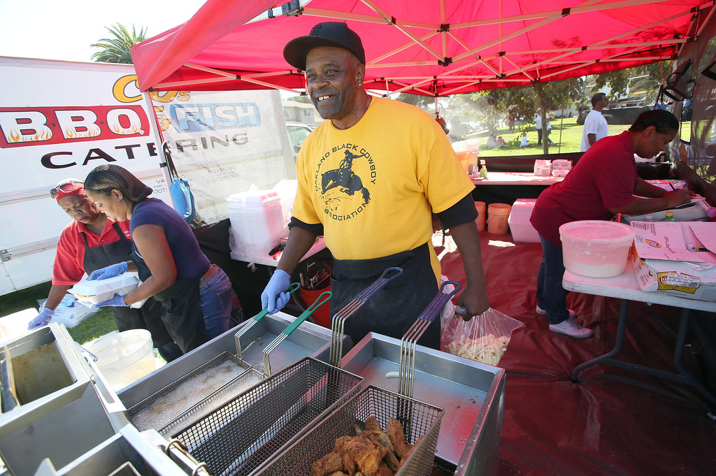 ". Charles ""C.J.\"" Evans, of Richmond, cooks catfish during the 39th annual Oakland Black Cowboy Parade and Heritage Festival at De Fremery Park in Oakland, Calif., on Saturday, Oct. 5, 2013. The event also featured food, entertainment and pony rides for kids. The Oakland Black Cowboy Association began in 1975 and educates the public about the role that black cowboys played in history and building of the west. (Jane Tyska//Bay Area News Group)"