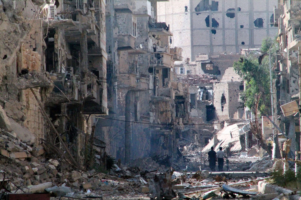 . Syrians walk down a destroyed street in the centre of Syria\'s northeastern city of Deir Ezzor on June 27, 2013. More than 100,000 people have been killed in Syria\'s uprising, a watchdog said, as a proposed Geneva peace conference looked set to be delayed, dimming hopes for an end to the bloodshed.   AHMAD ABOUD/AFP/Getty Images