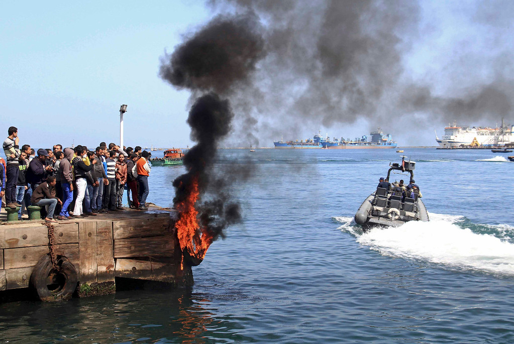 . Several protesters set fire to tires on the city\'s dock in an attempt to prevent ships from coming in to the strategic city of Port Said at the Mediterranean end of the Suez Canal, in Egypt, Saturday, March 9, 2013. (AP Photo/Ahmed Ramadan)