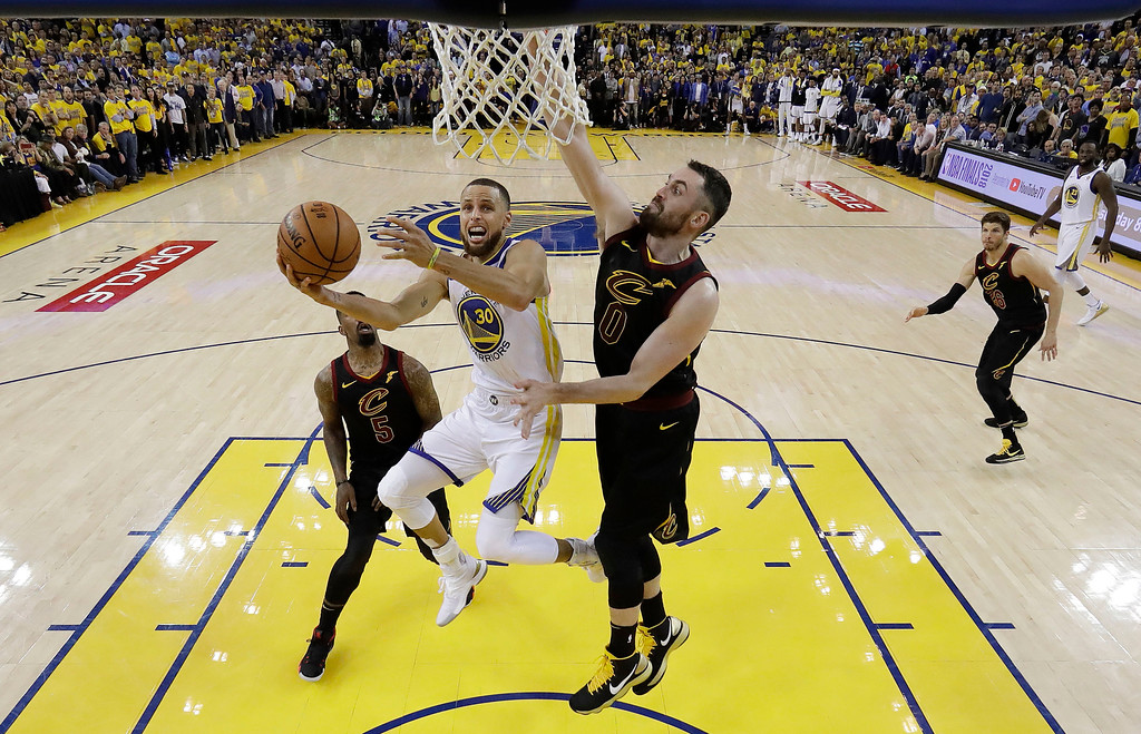 . Golden State Warriors\' Stephen Curry (30) drives to the basket as Cleveland Cavaliers\' Kevin Love (0) defends during the second half of Game 1 of basketball\'s NBA Finals Thursday, May 31, 2018, in Oakland, Calif. (AP Photo/Marcio Jose Sanchez)