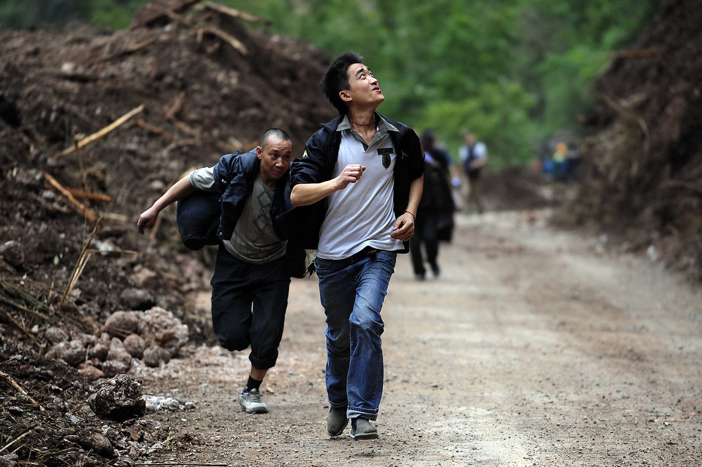 . People run during aftershocks to avoid falling rocks on their way to the city of Ya\'an, southwest China\'s Sichuan province. Clogged roads, debris and landslides impeded rescuers as they battled to find survivors of a powerful earthquake in mountainous southwest China that left at least 188 dead.   STR/AFP/Getty Images