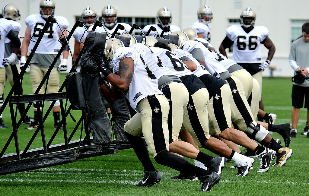 . New Orleans Saints linemen push the sled during NFL football training camp in White Sulphur Springs , W.Va., Sunday, July 27, 2014. (AP Photo/Chris Tilley)