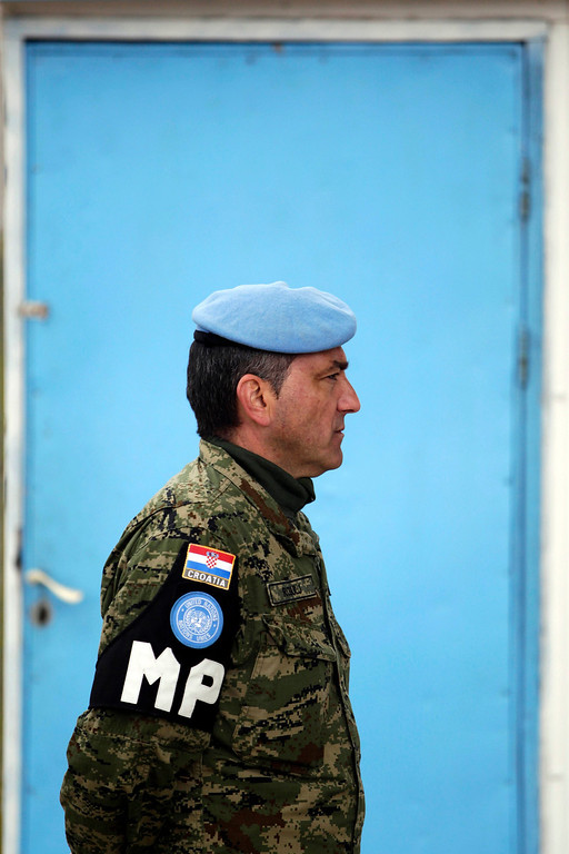 . A United Nations military police officer watches as trucks loaded with apples make their way across the Kuneitra border crossing between Israel and Syria March 5, 2013. Starting Tuesday about 18,000 tons of apples grown by farmers in the Golan Heights will be transferred across the border to Syria and marketed there, as part of a project initiated by the Israeli Ministry of Agriculture and Rural Development. Israel captured the Golan Heights in the 1967 Middle East war and annexed it in 1981 in a move not recognized internationally. REUTERS/Baz Ratner