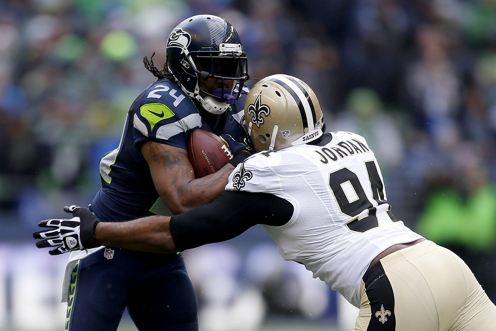 . SEATTLE, WA - JANUARY 11:  Running back Marshawn Lynch #24 of the Seattle Seahawks runs the ball against defensive end Cameron Jordan #94 of the New Orleans Saints in the first quarter during the NFC Divisional Playoff Game at CenturyLink Field on January 11, 2014 in Seattle, Washington.  (Photo by Otto Greule Jr/Getty Images)