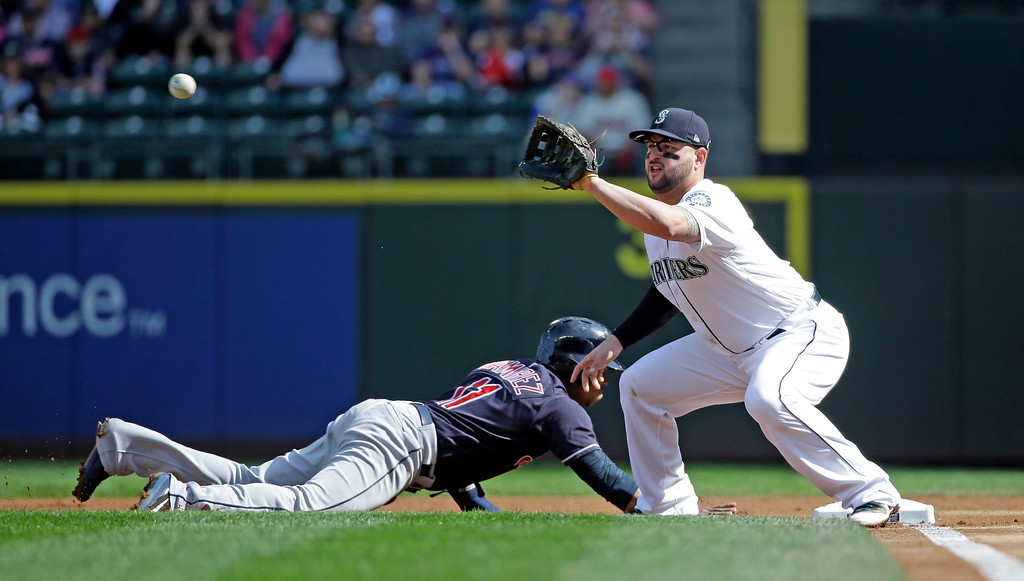 . Cleveland Indians\' Jose Ramirez, left, dives safely back to first base on a pick-off attempt as Seattle Mariners first baseman Yonder Alonso catches the ball in a baseball game Saturday, Sept. 23, 2017, in Seattle. (AP Photo/Elaine Thompson)