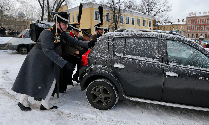 . Historical re-enactors dressed as 1812-era Russian imperial soldiers push a car from a battle field during a reenactment of the French Invasion of Russia in 1812, during celebrations to mark the Russian Orthodox Christmas in St. Petersburg, Russia, Monday, Jan. 7, 2013.  Christmas falls on Jan. 7 for Orthodox Christians who rely on the old Julian calendar rather than the  Gregorian calendar adopted by Catholics and Protestants and commonly used in secular life around the world. (AP Photo/Dmitry Lovetsky)