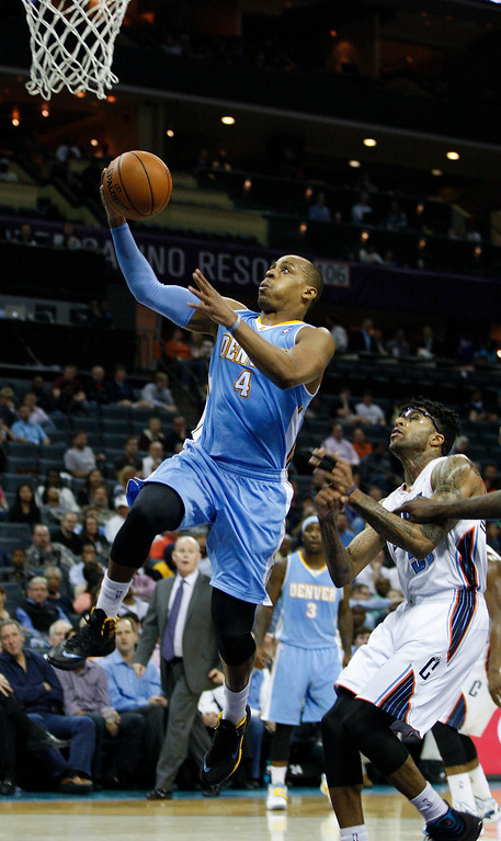 . Denver Nuggets guard Randy Foye (4) scores against Charlotte Bobcats guard Chris Douglas-Roberts during the second half of an NBA basketball game in Charlotte, N.C., Monday, March 10, 2014. Charlotte won 105-98. (AP Photo/Nell Redmond)