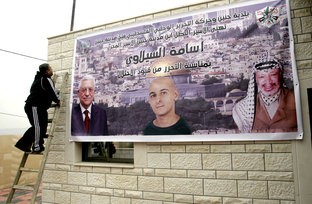 ". A Palestinian relative of Osama Al-Selawai hangs a poster with his picture in the middle, with pictures of Palestinian President, Mahmoud Abbas, left, and former President Yasser Arafat, right, at Al-Selawai\'s home in the West Bank city of Jenin, Monday, Dec. 30, 2013. Al-Selawai is one of 26 long-serving Palestinian prisoners who were convicted in connection to the killing of Israelis, that Israel announced  it will release this week under a U.S.-brokered formula to resume Mideast peace talks. Arabic reads, ""Jenin municipality and the Palestinian National Liberation Movement - Fatah (Jenin city), congratulates Jenin son, the free prisoner, Osama Al-Selawai, for his freedom from the shackles of occupation.\"" (AP Photo/Mohammed Ballas)"