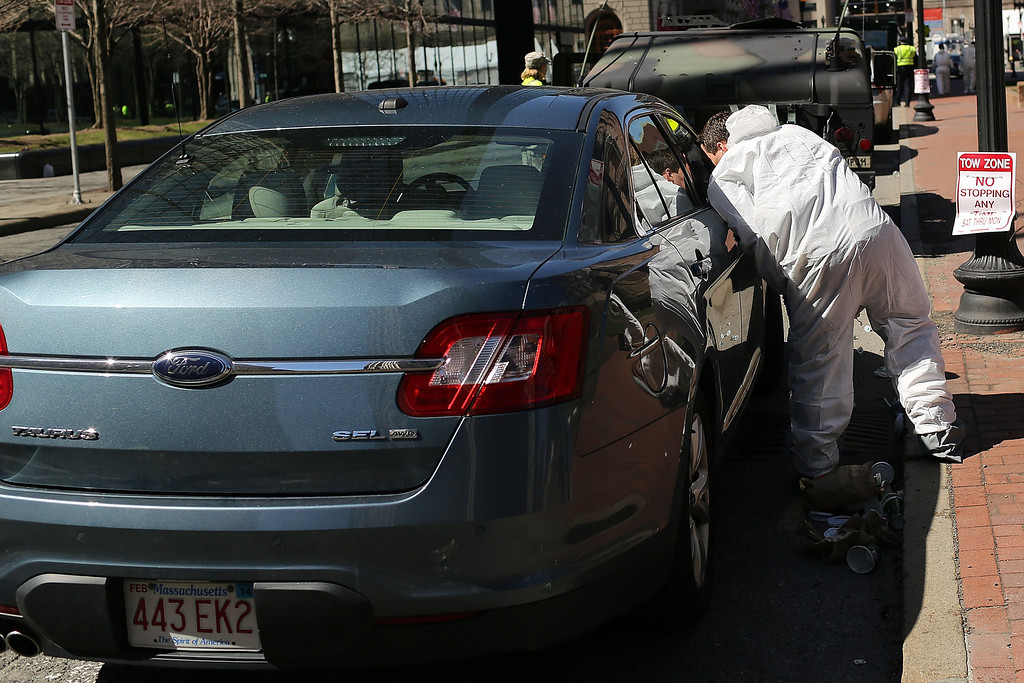 . Recovery workers, including members of the Federal Bureau of Investigation (FBI), search for clues near the scene of twin bombings at the Boston Marathon on April 17, 2013 in Boston, Massachusetts. The explosions, which occurred near the finish line of the 116-year-old Boston race on April 15, resulted in the deaths of three people with more than 170 others injured. Security has been heightened across the nation as the search continues for the person or people behind the bombings.  (Photo by Spencer Platt/Getty Images)