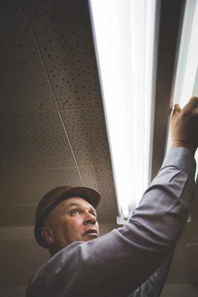 A man using his hands to install fluorescent bulbs.