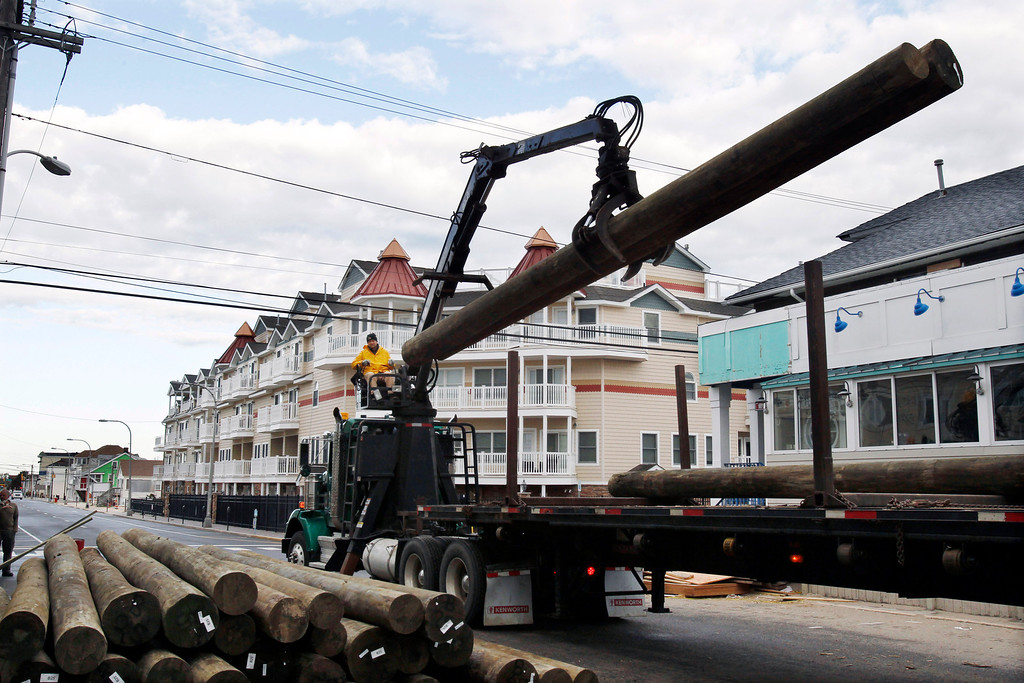 . Yuri Pismennyi unloads 36 poles to be used as pilings to rebuild the boardwalk in Seaside Heights, N.J., Thursday, April 25, 2013. Six months after Superstorm Sandy devastated the Jersey shore and New York City and pounded coastal areas of New England, the region is dealing with a slow and frustrating, yet often hopeful, recovery. (AP Photo/Mel Evans)