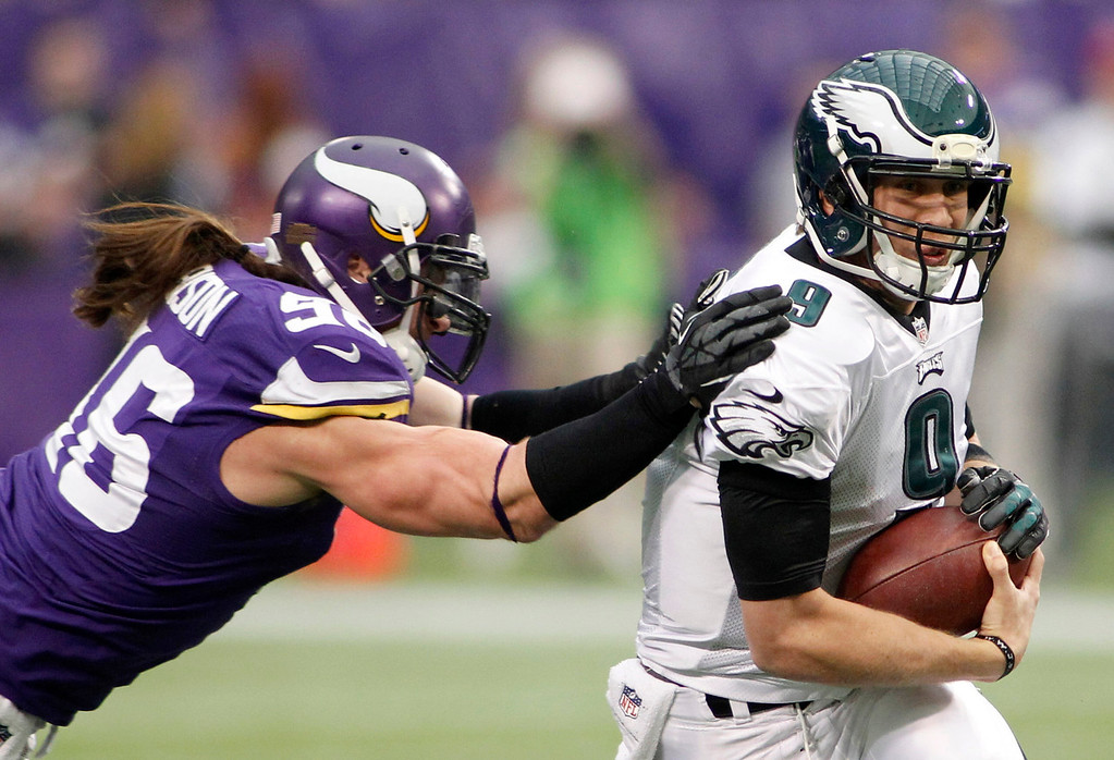 . Philadelphia Eagles quarterback Nick Foles, right, runs from Minnesota Vikings defensive end Brian Robison during the first half of an NFL football game, Sunday, Dec. 15, 2013, in Minneapolis. (AP Photo/Andy King)