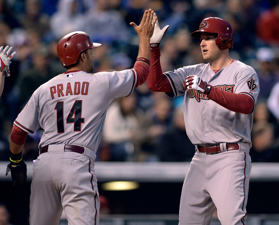 . DENVER, CO - APRIL 5:  Arizona slugger Mark Trumbo, right, slapped hands with Martin Prado after hitting a home run in the third inning. The Colorado Rockies hosted the Arizona Diamondbacks Saturday night, April 5, 2014 in Denver. (Photo by Karl Gehring/The Denver Post)