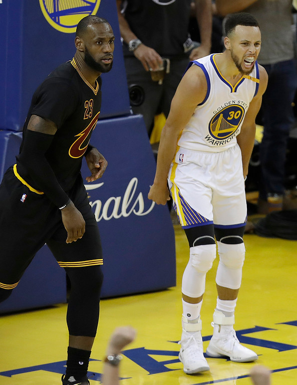. Golden State Warriors guard Stephen Curry (30) reacts after scoring next to Cleveland Cavaliers forward LeBron James during the second half of Game 2 of basketball\'s NBA Finals in Oakland, Calif., Sunday, June 4, 2017. (AP Photo/Marcio Jose Sanchez)