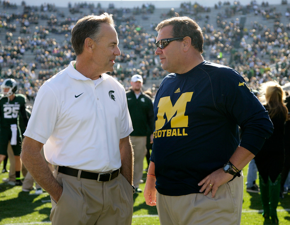 . Michigan State coach Mark Dantonio, left, and Michigan coach Brady Hoke talk at midfield before an NCAA college football game, Saturday, Oct. 25, 2014, in East Lansing, Mich. (AP Photo/Al Goldis)