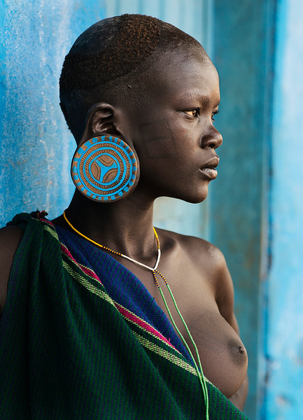 A young Suri woman wearing big traditional earrings. It is also traditional for women of this tribe to wear a lip plate although she has opted not to do this.  Southern Ethiopia, 2017