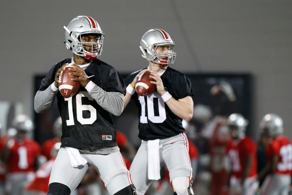 . Ohio State quarterbacks J.T. Barrett, left, and Joe Burrow drop back to pass during spring NCAA college football practice Tuesday, March 7, 2017, in Columbus, Ohio. (AP Photo/Jay LaPrete)