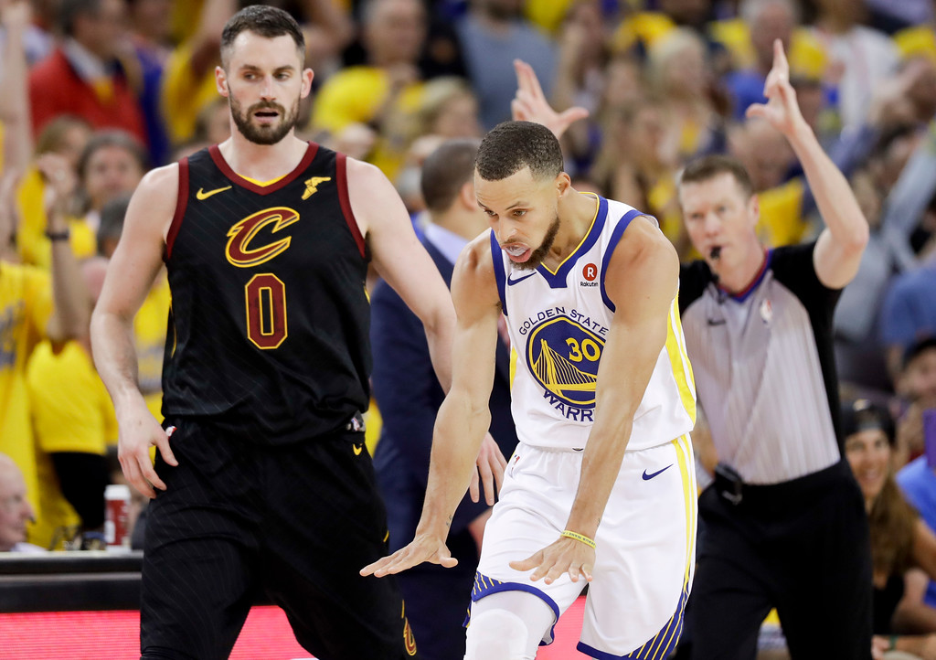 . Golden State Warriors guard Stephen Curry celebrates in front of Cleveland Cavaliers forward Kevin Love (0) during the second half of Game 1 of basketball\'s NBA Finals in Oakland, Calif., Thursday, May 31, 2018. (AP Photo/Marcio Jose Sanchez)