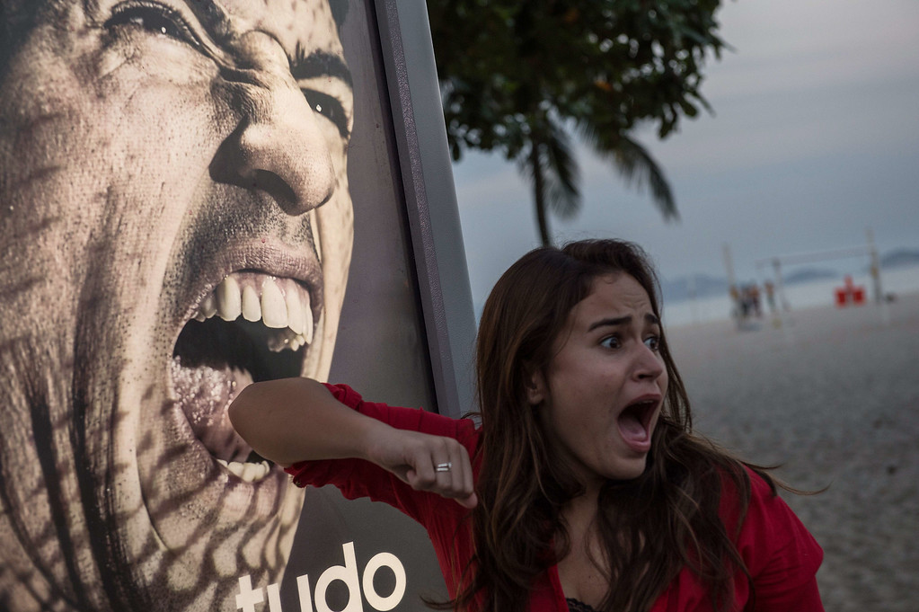 . A tourist jokes in front of an advertisement with the portrait of Uruguay\'s forward Luis Suarez at Copacabana beach in Rio de Janeiro, Brazil, on June 26, 2014. Sportswear giant Adidas said Thursday it would stop using Luis Suarez, one of its key promotional stars, for World Cup adverts after his four-month ban from football activities for biting Italian Giorgio Chiellini. AFP PHOTO / YASUYOSHI CHIBA/AFP/Getty Images