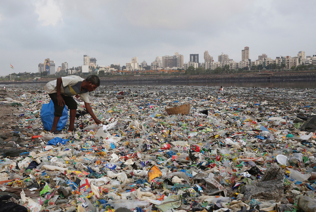 ". A man collects plastic and other recyclable material from the shores of the Arabian Sea, littered with plastic bags and other garbage, in Mumbai, India, Monday, June 4, 2018. The theme for this year\'s World Environment Day, marked on June 5, is ""Beat Plastic Pollution.\"" (AP Photo/Rafiq Maqbool)"