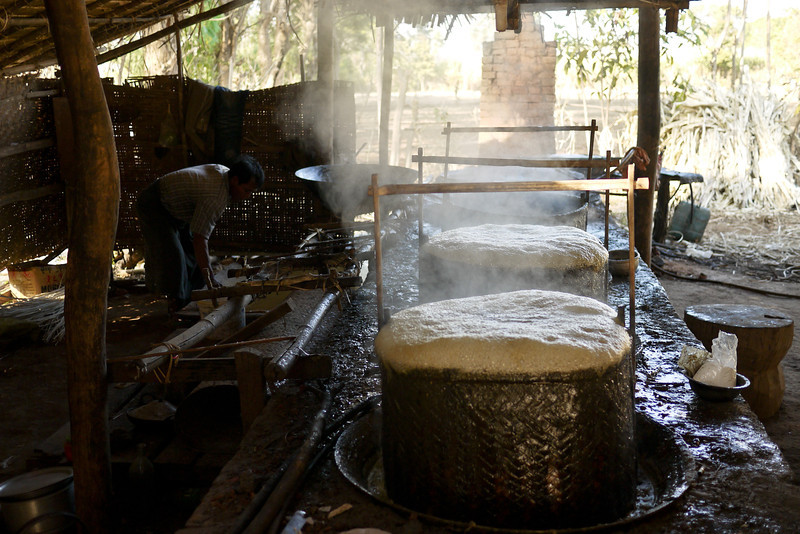 Huge boiling vats of sugarcane juice are thickening so they can turn into Burmese sweets, Inle Lake, Burma (Myanmar).
