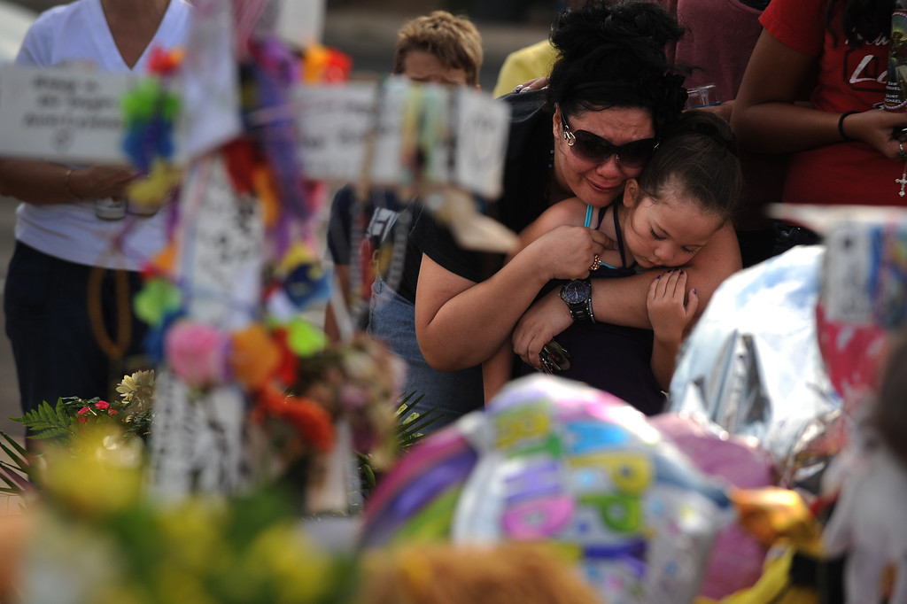 . Gina Martinez hugs her daughter Aaron Martinez, 5, while looking at the memorial for young shooting victim Veronica Moser, 6, on July 27, 2012. Martinez is from Aurora and says she takes her kids to the Century 16 theatre all the time. Mourners continue to pay their respect at the site of the memorial. Helen H. Richardson, The Denver Post