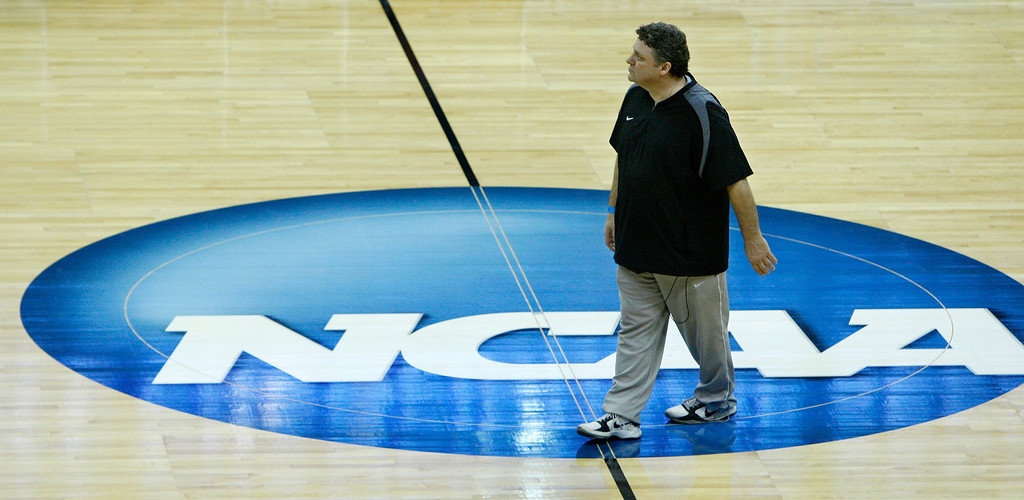 . Oakland head coach Greg Kampe walks across the NCAA logo during a practice for the West regional second round NCAA college basketball tournament in Tulsa, Okla., Thursday, March 17, 2011. (AP Photo)
