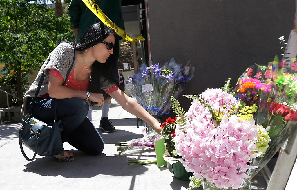 . A woman leaves flowers at a makeshift memorial for victims of a balcony that collapsed in Berkeley, Calif., Tuesday, June 16, 2015. Berkeley police said several people were killed and others injured after a balcony fell shortly before 1 a.m., near the UC Berkeley campus. (AP Photo/Jeff Chiu)