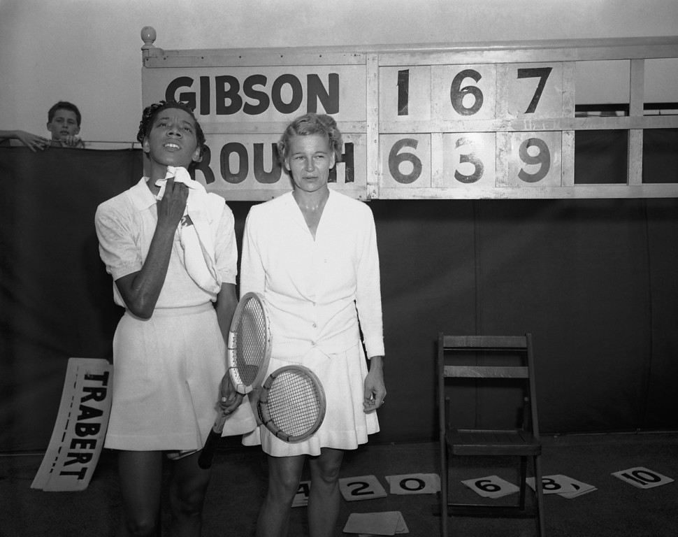 . Tennis player Althea Gibson, left, of New York, wipes her face as she stands with Louise Brough, of Beverly Hills, Calif., who eliminated Gibson in the second round match of the National Tennis Championships in Forest Hills, New York, Aug. 30, 1950. Brough, Wimbledon champion, won 6-1, 3-6, 9-7. Gibson, the first African American ever to play in the event, led by seven games to six when play resumed in the third set of the match, which was rained out the day before. (AP Photo)