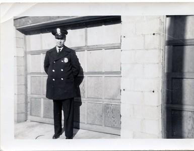Harry Miller by garage in uniform