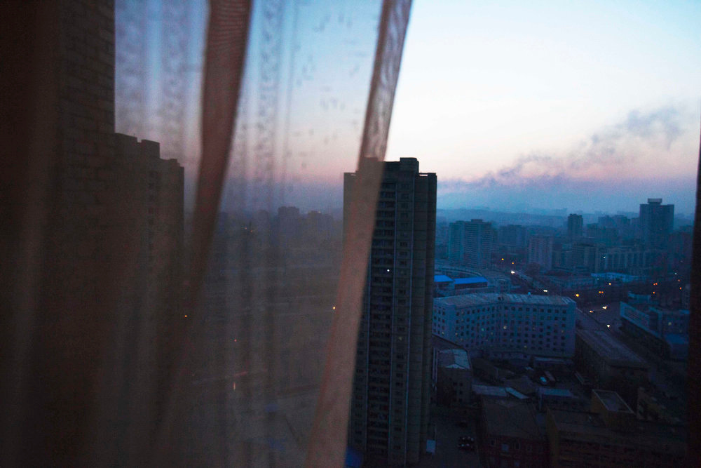 Description of . Central Pyongyang, North Korea at dusk through a hotel room window on April 12, 2011.  (AP Photo/David Guttenfelder)