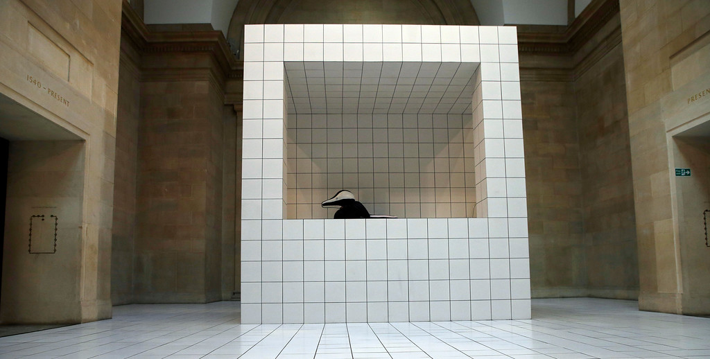 . A performer in a squash-like costume as part of a new work of art by Anthea Hamilton, during a press pre-view at the Tate Britain in London, Wednesday, March 21, 2018. Over 7000 white tiles have been laid in the large galley with selected works from the Tate\'s collection, chosen for their organic form, the tiles formed in to podiums which the performer uses to interact with the work.(AP Photo/Alastair Grant)