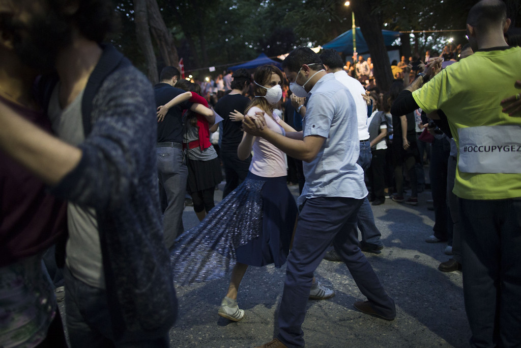 . Protestors dance Tango at the Gezi park in Taksim Square on June 6, 2013 in Istanbul, Turkey. The protests began initially over the fate of Taksim Gezi Park, one of the last significant green spaces in the center of the city. The heavy-handed viewed response of the police, Prime Minister Recep Tayyip Erdogan and his government\'s increasingly authoritarian agenda has broadened the rage of the clashes.  (Photo by Uriel Sinai/Getty Images)