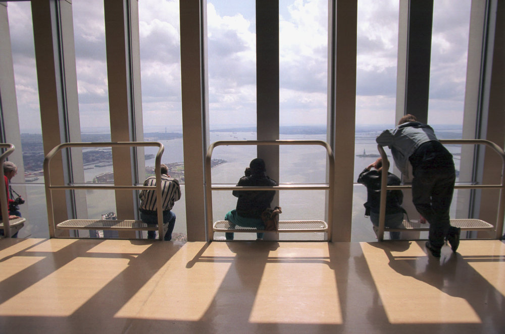 Description of . Visitors peer out across a sunny Upper New York Bay from the 107th floor observation deck of New York's World Trade Center on Saturday, April 17, 1993.  The lookout has reopened after being closed for seven weeks following the Feb. 26 bombing at the basement of the twin towers.  (AP Photo/Justin Sutcliffe)