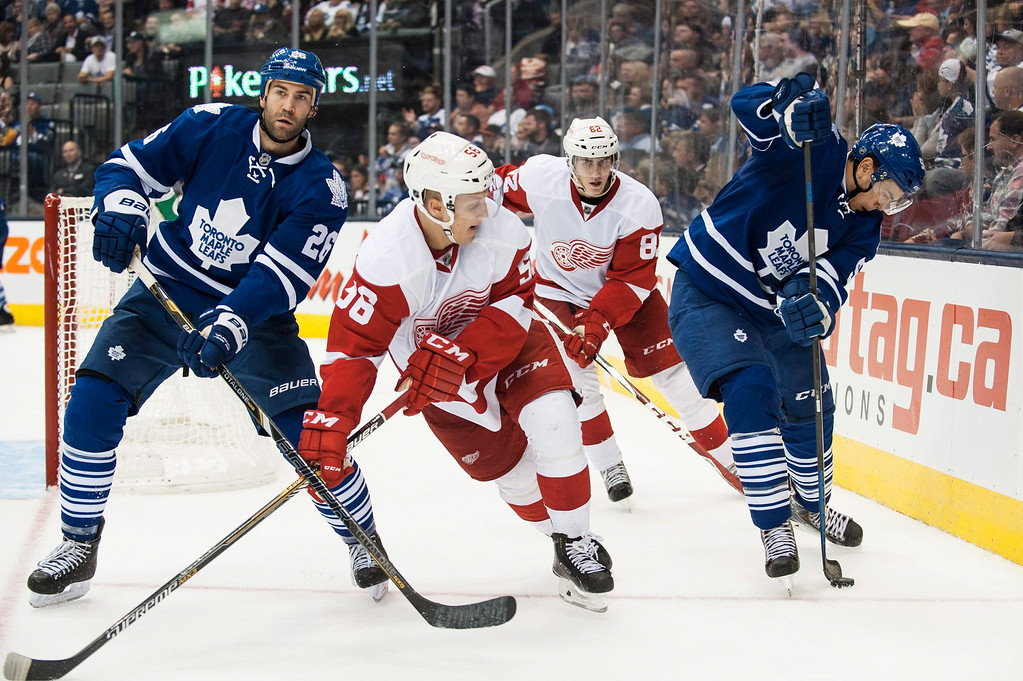 . Toronto Maple Leafs\' Staurt Percy, right, battles for the puck against Detroit Red Wings\' Tomas Nosek, second from right, and Teemu Pulkkinen, second from left, during third-period preseason NHL hockey game action in Toronto, Friday, Oct. 3, 2014. (AP Photo/The Canadian Press, Aaron Vincent Elkaim)
