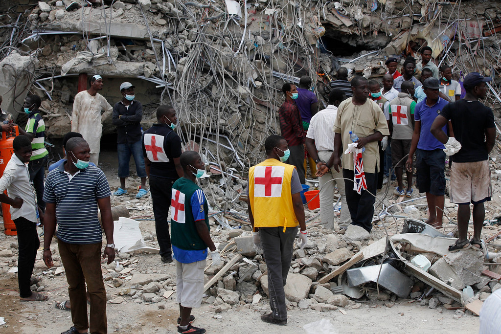 . Rescue workers gather at the site of a collapsed building belonging to the Synagogue Church of All Nations in Lagos, Nigeria, Saturday, Sept, 13. 2014. The building was being extended, adding 2 additional floors when it collapsed. (AP Photo/Sunday Alamba)