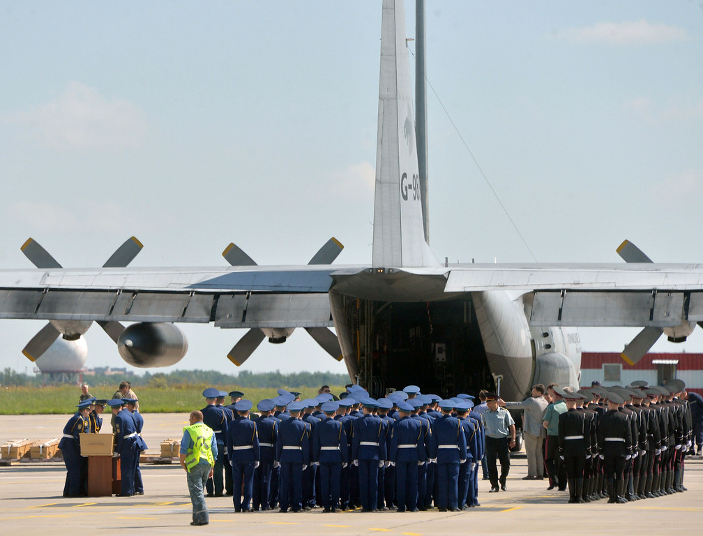 . Ukrainian servicemen (L) carry a coffin that contains the body from downed Malaysia Airlines flight MH17 during a ceremony in Kharkiv on July 23, 2014. The first plane carrying bodies from downed Malaysia Airlines flight MH17 on July 23 left eastern Ukraine for the Netherlands. The Dutch military aircraft took off from the airport in the government-controlled city of Kharkiv bound for Eindhoven after the first group of victims\' remains were loaded onto the plane in wooden coffins. AFP PHOTO/ GENYA  SAVILOV/AFP/Getty Images