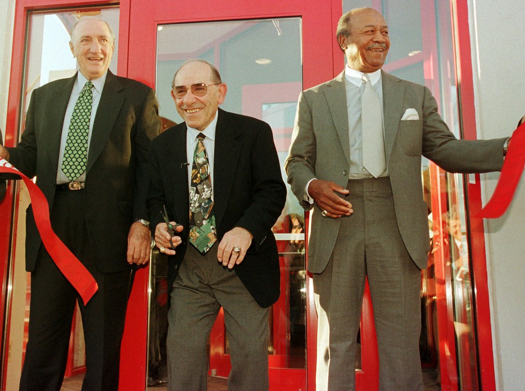 . New York Yankees Hall of Famer Yogi Berra, center, laughs after cutting a ribbon at the opening of The Yogi Berra Museum at Montclair State University in Upper Montclair, N.J., Friday, Oct. 23, 1998. Berra is flanked by former Brooklyn Dodgers pitcher Ralph Branca, left, and fellow Hall of Famer Larry Doby. (AP Photo/Mike Derer)