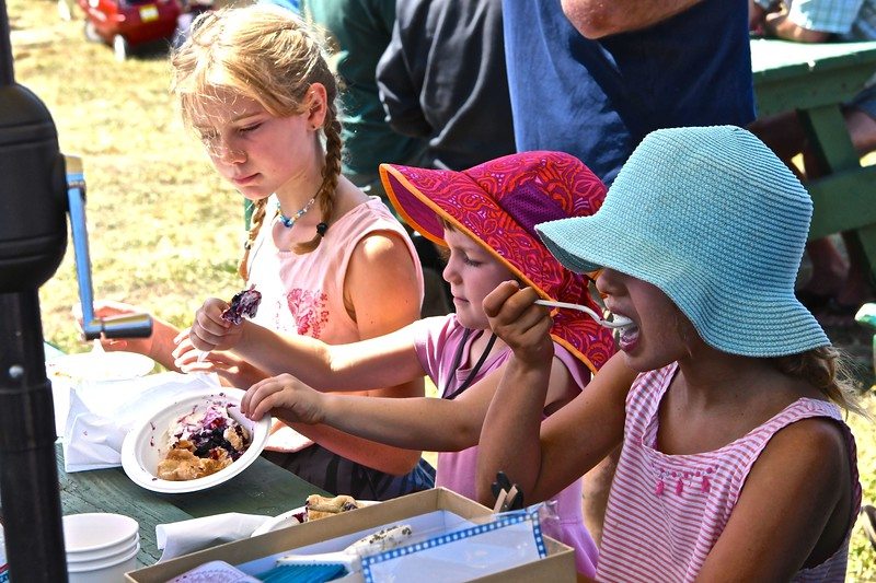 Emma McBurney and sister Lyla McBurney bookend their friend Maeve as they enjoy fresh blackberry pie and ice cream on Sunday at the Westhaven Wild Blackberry Festival. José Quezada—For the Times-Standard
