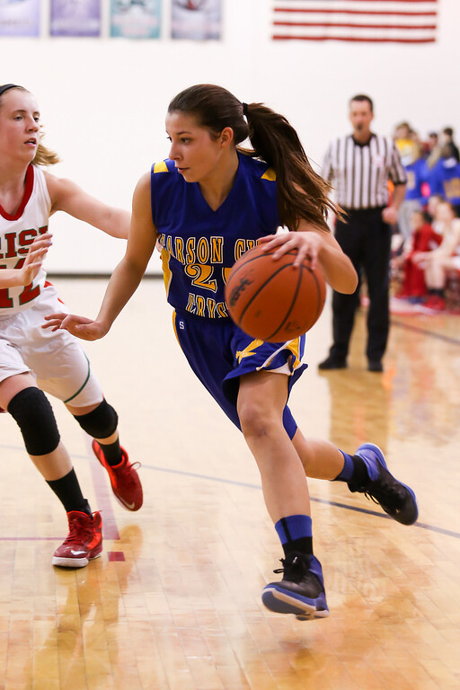 . Carson City-Crystal sophomore Jenna Schneider, (20) drives the ball as Megan English, (12) plays defense at Sacred Heart Thursday, Jan. 23, 2014. Carson City-Crystal won 50-23.  (Sun photo by KEN KADWELL/@KenKadwell).