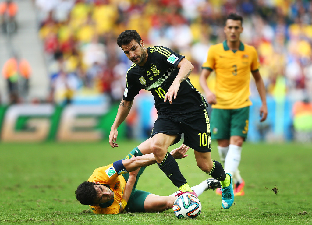 . Cesc Fabregas of Spain is challenged by Mile Jedinak of Australia during the 2014 FIFA World Cup Brazil Group B match between Australia and Spain at Arena da Baixada on June 23, 2014 in Curitiba, Brazil.  (Photo by Jeff Gross/Getty Images)