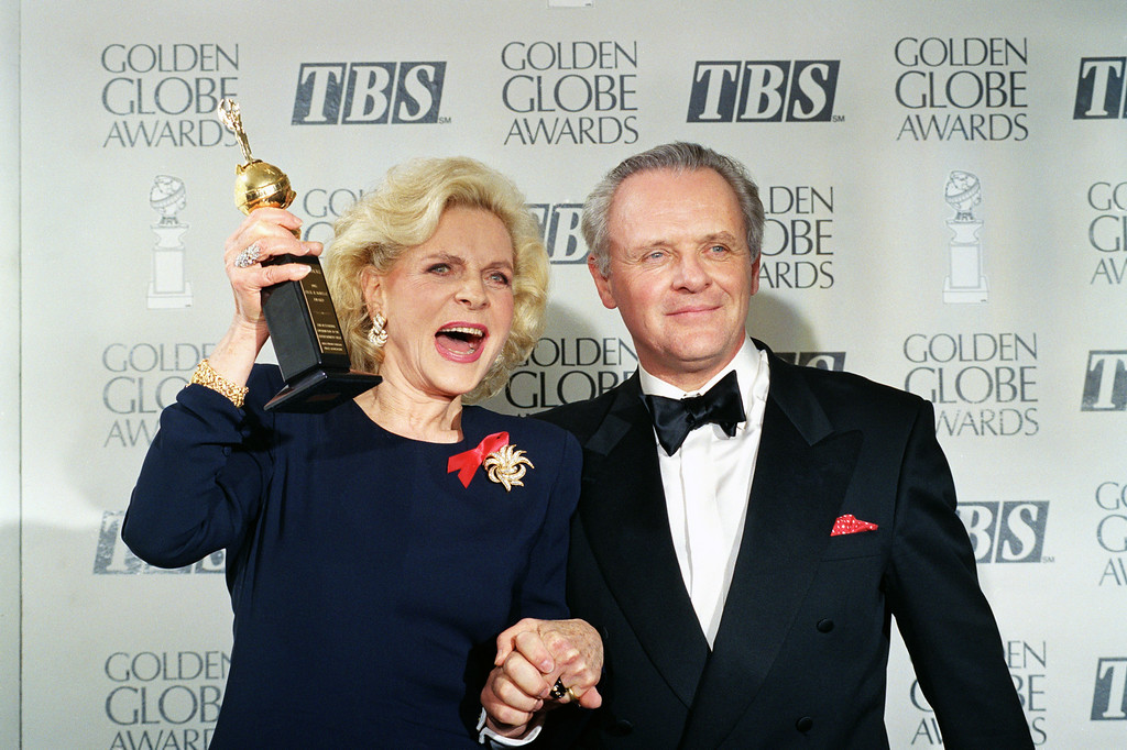 . FILE - This Jan. 23, 1993 file photo shows actress Lauren Bacall holding up her Cecil B. DeMille Award for Lifetime Achievement as she holds hands with actor Anthony Hopkins backstage at the 50th annual Golden Globe Awards in Beverly Hills, Calif. Bacall, the sultry-voiced actress and Humphrey Bogart�s partner off and on the screen, died Tuesday, Aug. 12, 2014 in New York. She was 89. (AP Photo/Reed Saxon, File)