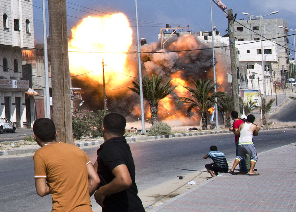 . Palestinian men look on as a bomb from an Israeli air strike hits a house in Gaza City on August 23, 2014.  Israel kept up the pressure on Hamas in Gaza, carrying out multiple air strikes that killed six Palestinians, five of them from the same family, as Egypt prepared to convene new truce talks. AFP PHOTO/ ROBERTO  SCHMIDT/AFP/Getty Images