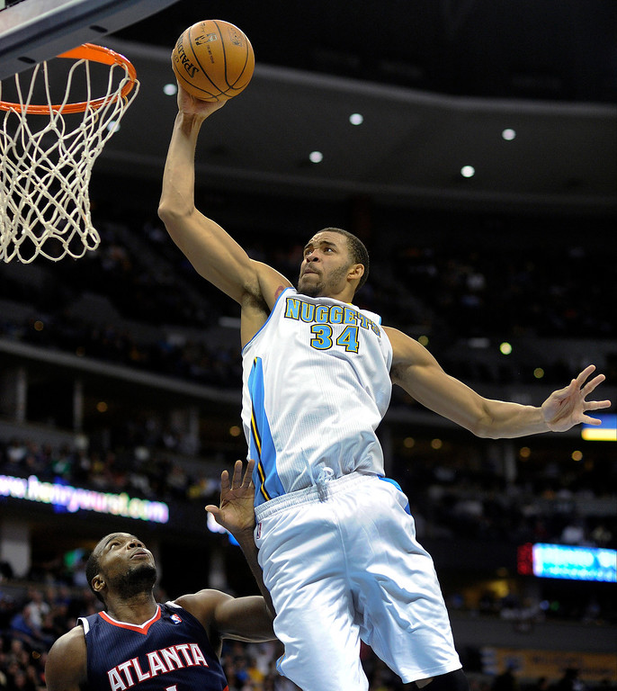 . Denver center JaVale McGee (34) flew above the rim, and Atlanta defender Paul Millsap (4) to score in the first half.   Photo By Karl Gehring/The Denver Post