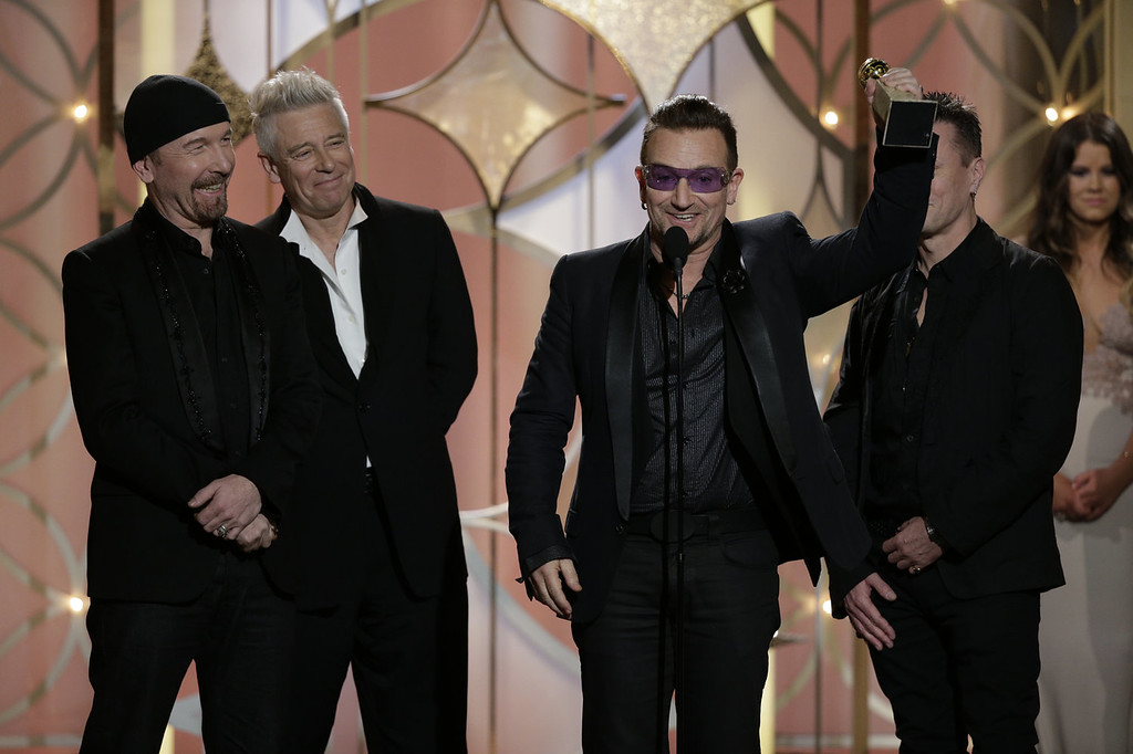 """. In this handout photo provided by NBCUniversal, (L-R) The Edge, Adam Clayton, Bono and Larry Mullen, Jr. of U2, accept the award for Best Original Song - Motion Picture for \""""Ordinary Love\"""" from \""""Mandela: Long Walk to Freedom\"""" during the 71st Annual Golden Globe Award at The Beverly Hilton Hotel on January 12, 2014 in Beverly Hills, California.  (Photo by Paul Drinkwater/NBCUniversal via Getty Images)"""