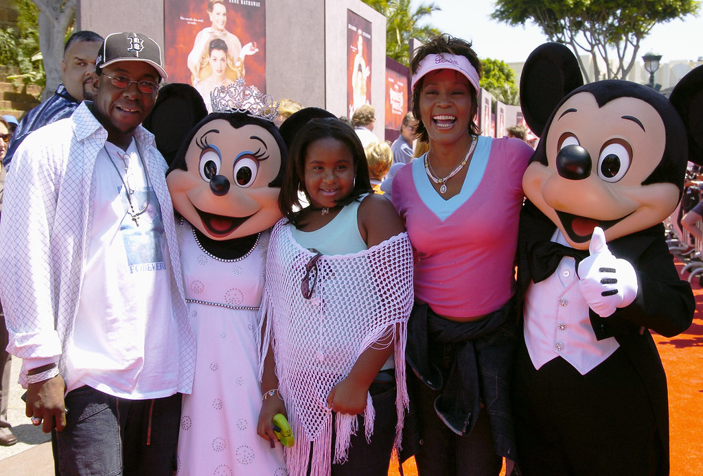 ". In this handout image provided by Disney Parks, Whitney Houston, Bobby Brown and their daughter Bobbi Kristina are greeted by Mickey Mouse and Minnie Mouse for the premiere of ""The Princess Diaries 2\"" at the Disneyland Resort August 7, 2004 in Anaheim, California.  (Photo by Lisa Rose/Disney Parks via Getty Images)"