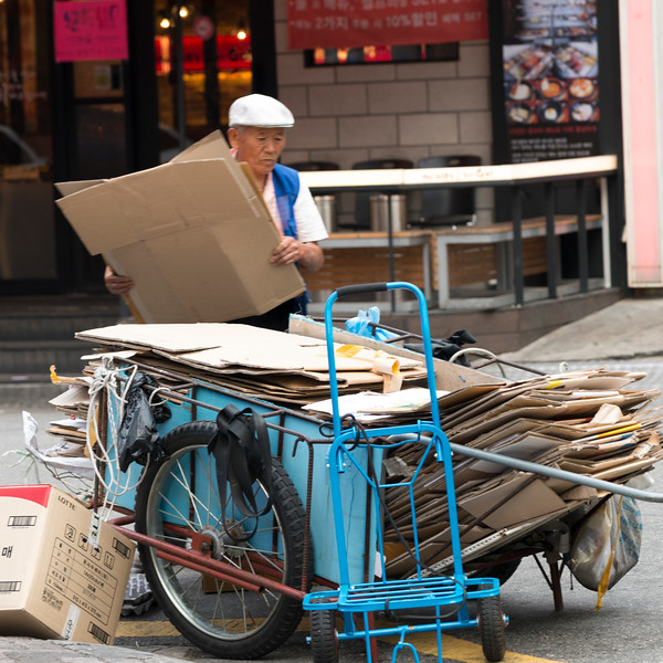 Man loading cardboards on cart, Seoul, South Korea