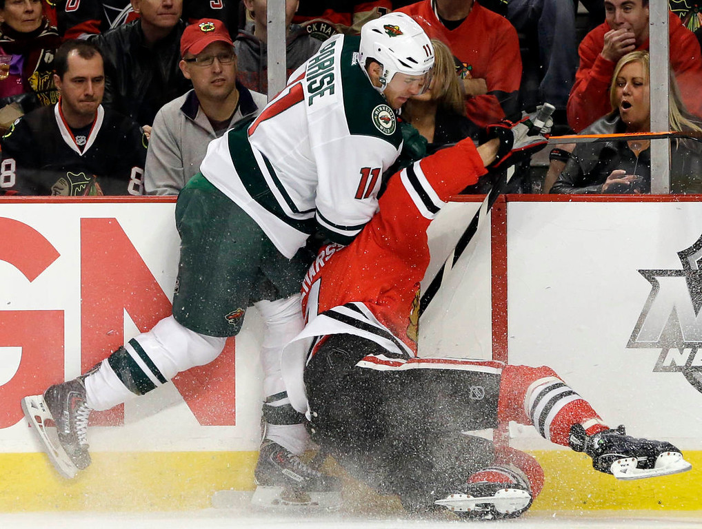 . Chicago Blackhawks\' Niklas Hjalmarsson (4), right, is checked by Minnesota Wild\'s Zach Parise (11) during the first period. (AP Photo/Nam Y. Huh)
